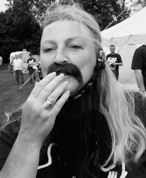 Picture of a pretty young lady with a false beard trying to infiltrate Bloke Fest.