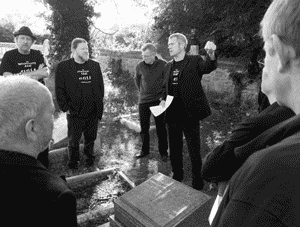 Men singing  at the grave of Alfred Williams.